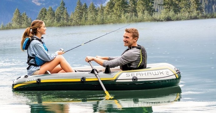 two people sitting in an inflatable kayak