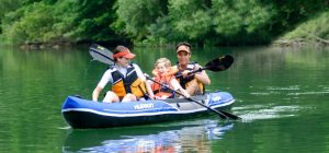 three people sitting in inflatable kayak